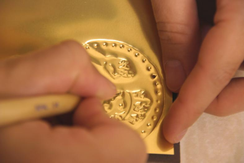 Embossing on metal sheets for the making of the Prince Coin, for The Prince of Hampshire (2006). Image © Gil Dekel.